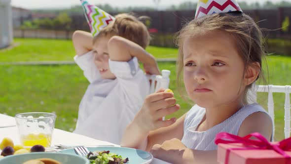 Cute Kids in Party Hats Talking with Family at Dinner Table