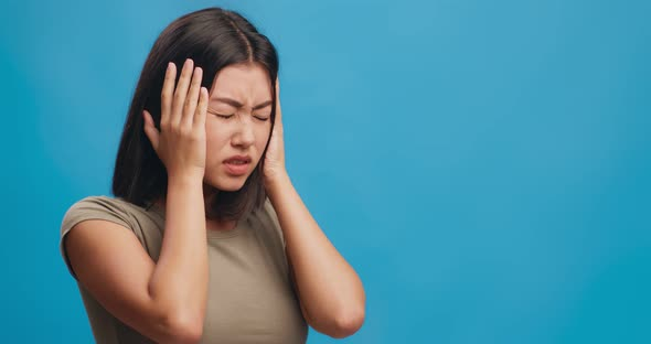Young Asian Woman with Headache Suffering From Noise, Closing Ears with  Palms, Blue Background by Prostock-studio