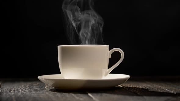Cup of Hot Coffee. Steam Coming Out of a Coffee Cup Standing on a White Saucer on a Wooden Table