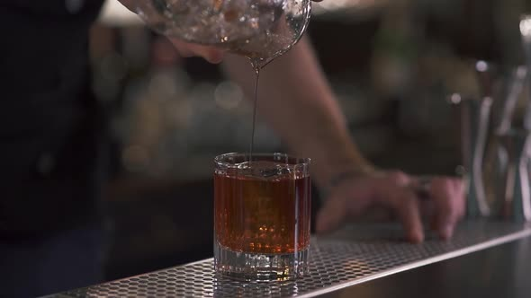 Male Hand Bartender Pours Liquid in the Glass with Big Ice Cube in It