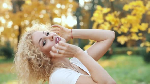 Beautiful Blonde Woman Touching Curly Hair, Walking in Autumn Park